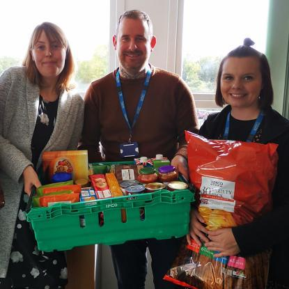 Staff at Housing Plus Group are pictured with donations to local food banks