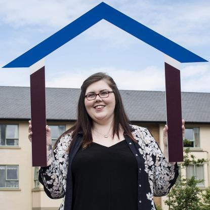 Customer Danielle Harrison holding part of the Housing Plus Group logo